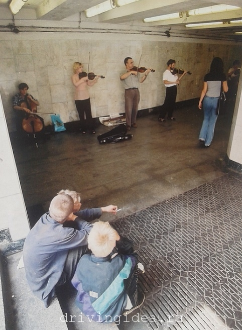 Boys listening to a violinists and cellist concert in the underpass